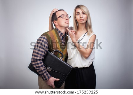 Scared nerd with his beautiful girl, studio shoot - stock photo