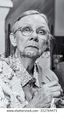 Scared old woman with crochet in living room - stock photo