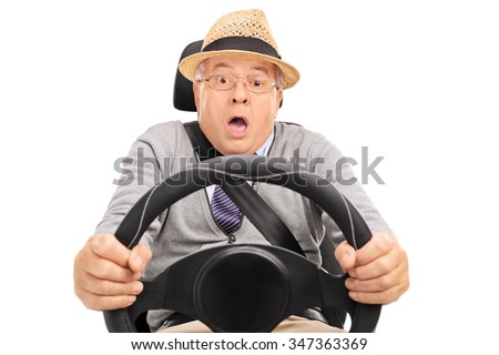 Scared senior holding a steering wheel and pressing the brake pedal to avoid a car crash isolated on white background - stock photo