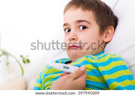 Scared sick boy with fever in the bed at home getting a body temperature measurement. - stock photo