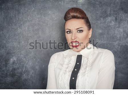 Scared teacher woman in white blouse on the blackboard background - stock photo
