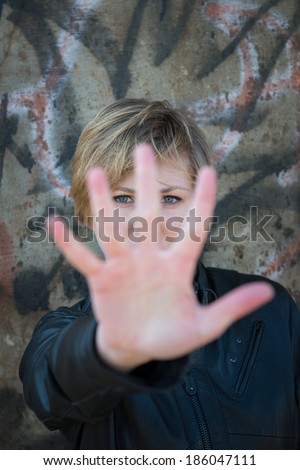 Scared teen girl holds up hand towards camera to say 'stop' - stock photo