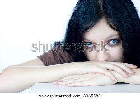 Scared teenage girl sitting near the table looking at you isolated on white - stock photo