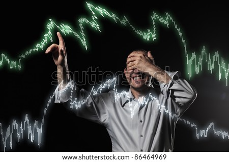 Scared trader pointing to stock market charts with eyes closed. Uncertainty concept photo. - stock photo