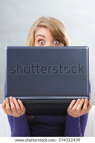Scared woman hiding behind her laptop and looking out from behind computer, modern technology - stock photo