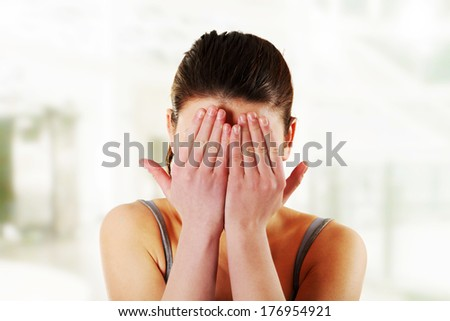 Scared woman hiding her face in hands - stock photo
