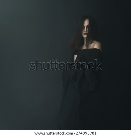 Scared woman in black in the fog - stock photo
