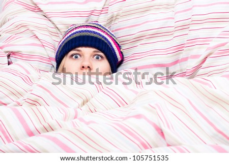 Scared woman in winter hat hiding wrapped in duvet. - stock photo