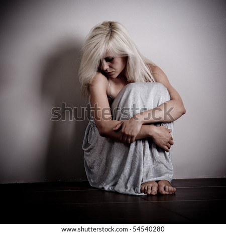 Scared woman sitting by the empty wall - stock photo