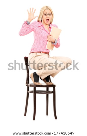 Scared woman standing on a chair isolated on white background - stock photo