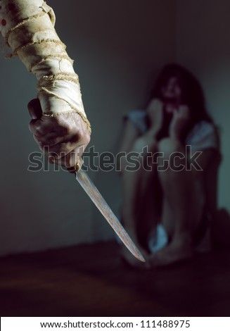 Scared woman threatened by a man with bloody knife - stock photo
