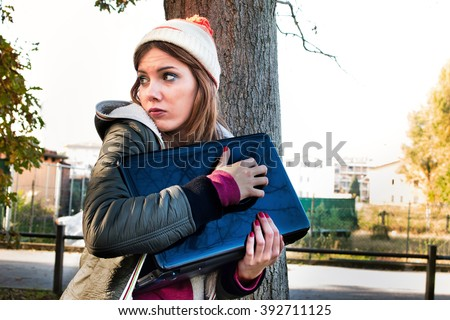 scared woman trying to protect her laptop pc and data looking helpless and vulnerable - privacy and identity theft concept - custom color tones and contrast effects added to add drama - stock photo