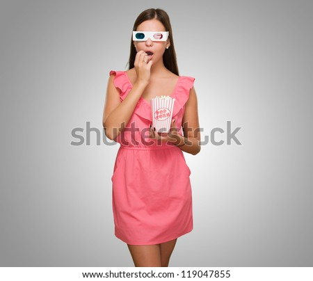 Scared Woman Watching 3d Movie against a grey background - stock photo