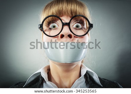 Scared woman with mouth taped shut. Afraid young girl with duct tape on lips. Censorship and freedom of speech concept. - stock photo