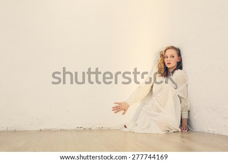 Scared young beautiful woman with curly hair sitting near white wall in the room - stock photo