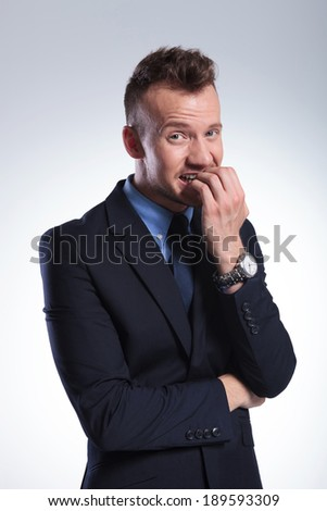 scared young business man biting his nails while looking into the camera. on a light gray studio background
