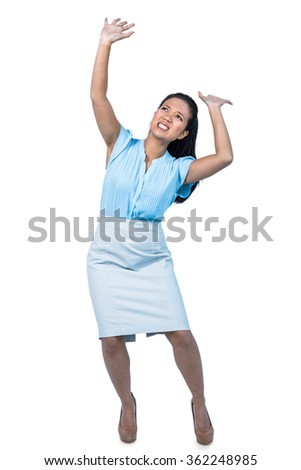 Scared young businesswoman holding something against white background - stock photo