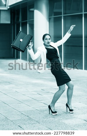 Scared young businesswoman with briefcase and gesturing fear on city background - stock photo