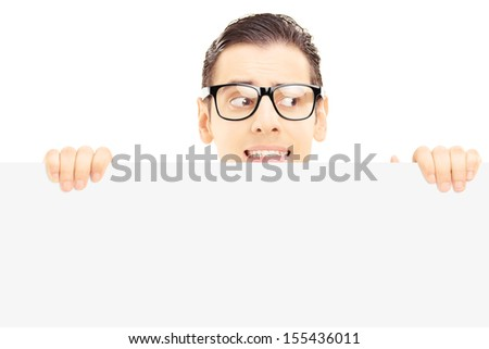 Scared young male with glasses hiding behind a blank panel isolated against white background - stock photo