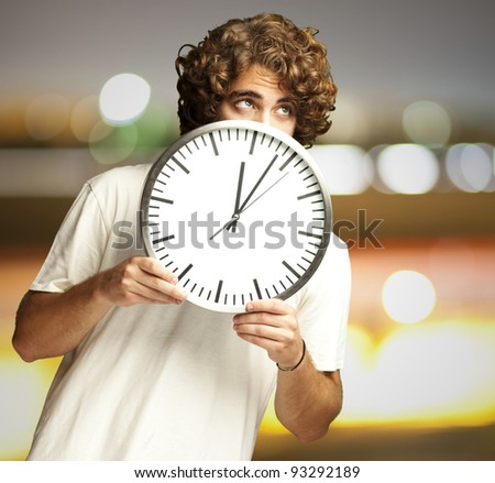scared young man hidden behind a clock against a city by night - stock photo
