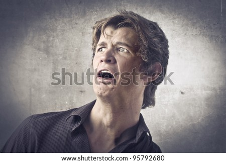 Scared young man screaming - stock photo