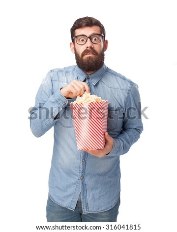 scared young man with popcorn - stock photo