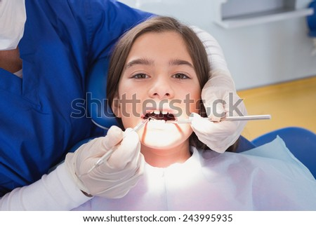 Scared young patient in dental examination in clinic - stock photo