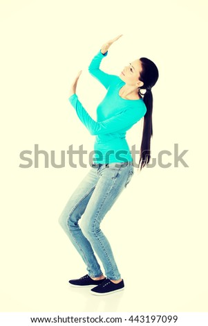 Scared young woman afraid of something above her - stock photo