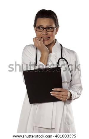 scared young woman doctor on a white background - stock photo