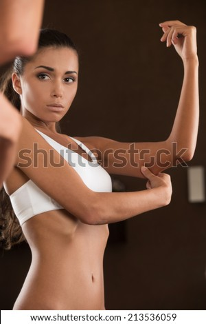 scared young woman looking at her arm. beautiful girl standing without clothing iand looking into mirror - stock photo
