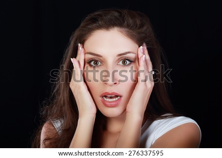 scared young woman over dark backround - stock photo