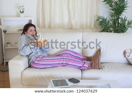 Scared young woman throwing popcorn while watching film on couch at home - stock photo