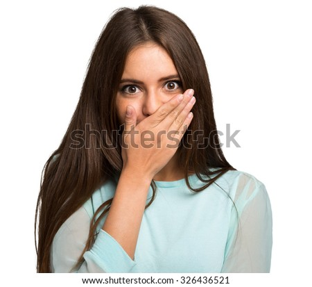 Scared young woman with her hand closing her mouth - stock photo