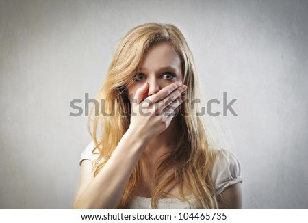 Scared young woman with her hand on her mouth - stock photo