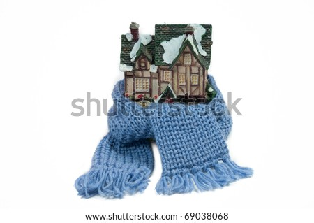 Scarf around a miniature small half-timbered house (conceptual view of protecting or isolating house) - stock photo