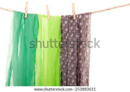 scarfs hanging on a rope clothesline isolated on white - stock photo