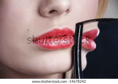 Scarlet lips are reflected in a little mirror which a girl holds in a hand