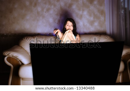 scarred beautiful girl watching TV on a couch - stock photo
