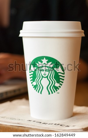 SCARSDALE, NY - SEPTEMBER 15, 2013: A tall Starbucks coffee in front of a woman working on a laptop computer. - stock photo
