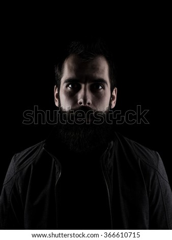 Scary bearded man staring at camera. Low key dark shadow portrait isolated over black background. - stock photo