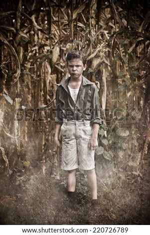 Scary boy in a cornfield holding a hatchet - stock photo