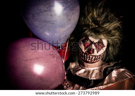 Scary Clown holding balloons in dark shadows - stock photo