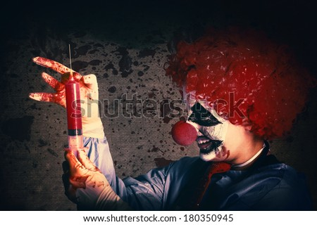 Scary clown holding large injection needle filled with human vaccine test trials. Bad medicine - stock photo