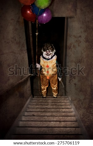 Scary Clown standing at the bottom of a stairway holding balloons and a knife - stock photo