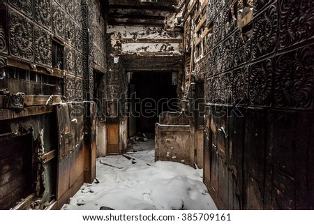 Scary corridor inside burned house decay rust garbage - stock photo