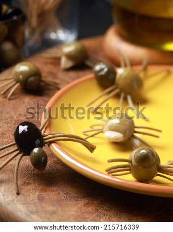 Scary creepy Halloween spider snacks served at a festive party made from cured green and black olives with pasta legs crawling all over the table from a yellow plate - stock photo