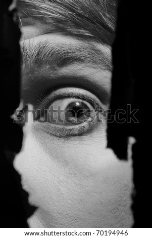 Scary eyes of a man spying through a hole in the wall - stock photo