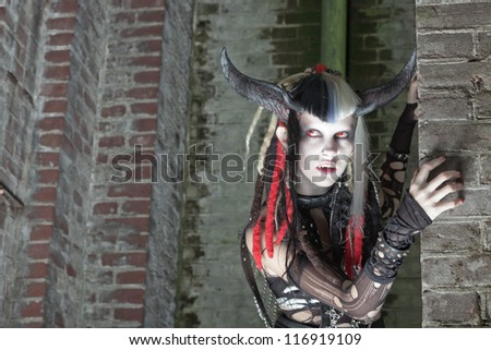Scary female demon in front of old dirty brick wall. - stock photo