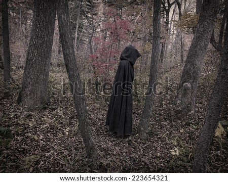 Scary figure in black mantle in the autumn forest, desaturated image - stock photo
