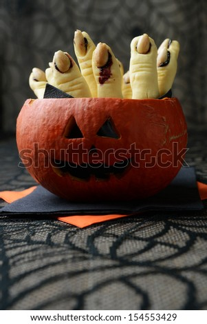 scary finger cookies in a pumpkin for halloween - stock photo